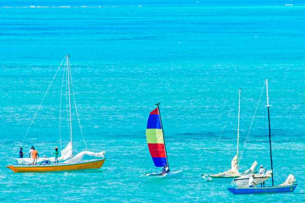 two Caicos Sloop sailboats and a Hobie Cat in the Bight at the Fool's Regatta