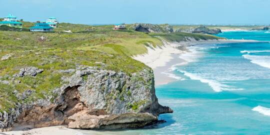 Cliffs by the sea at Mudjin Harbour, Middle Caicos, with small resort villas perched on top.