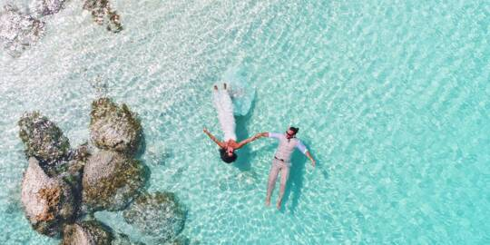 bride and groom floating on Grace Bay