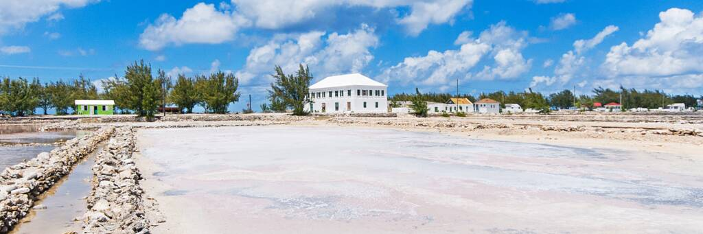 Salt ponds and walls with the white Harriot House in the distance on Salt Cay.