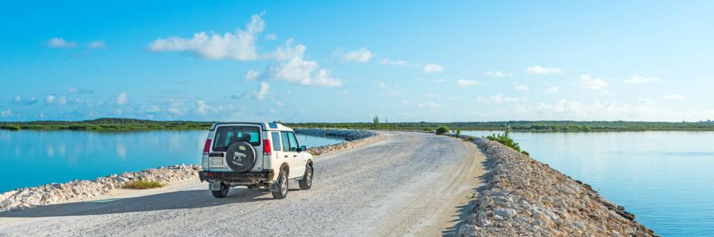 A white Land Rover Discovery vehicle driving across the causeway to Middle Caicos.