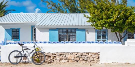 Quaint white and blue house with a bicycle in front on Salt Cay.