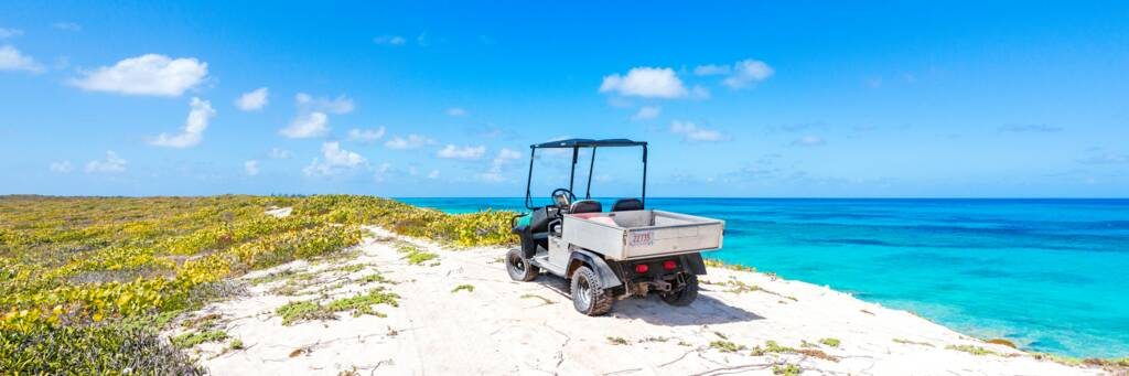 An offroad golf-cart parked on a bluff overlooking the ocean on Salt Cay.