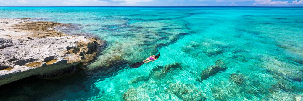 Snorkeler in clear turquoise water in the Turks and Caicos