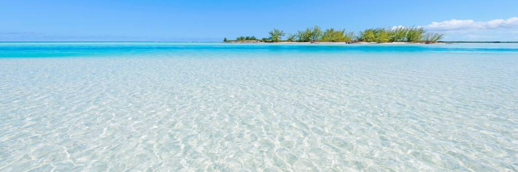 Clear waters of Horsestable Beach on North Caicos, with a small island in the distance.
