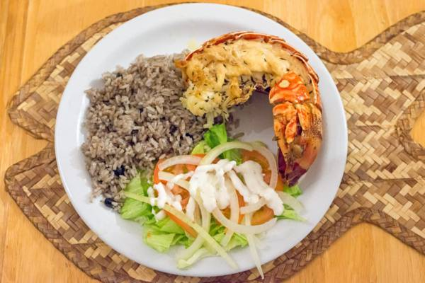 spiny lobster tail, peas and rice, and salad dinner at Daniel's Cafe on Middle Caicos
