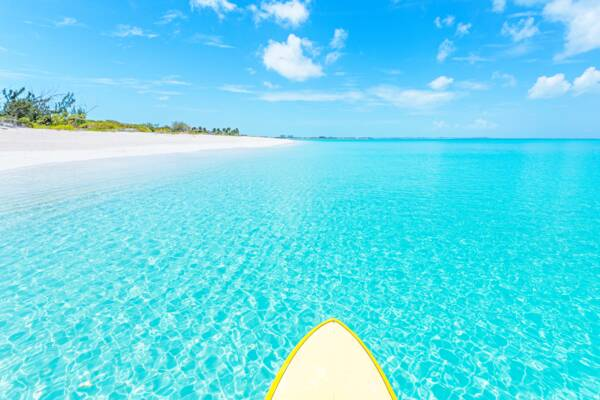 paddle board in clear turquoise water at Leeward Beach in the Turks and Caicos