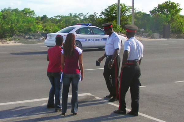 Turks and Caicos police officers at the scene of a car crash on Leeward Highway on Providenciales