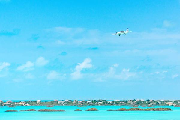 small twin turbo prop plane approaching the Providenciales International Airport over Chalk Sound