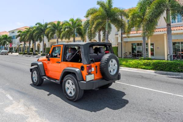 orange rental Jeep Wrangler driving on Grace Bay Road on Providenciales