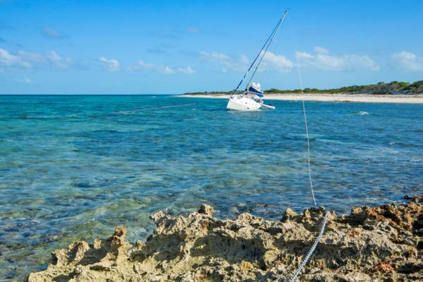 small yacht sailboat grounded on a shoal at Northwest Point on Providenciales