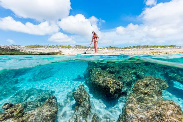 amazing clear ocean water and paddle boarder in the Turks and Caicos