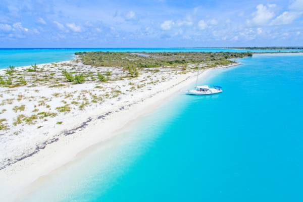 the beautiful beach and charter tour sailboat at Fort George Cay in the Turks and Caicos