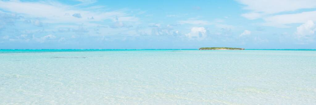 shallow and clear ocean water at Bambarra Beach with Pelican Cay on the horizon