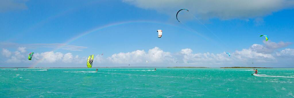 rainbow and kiteboarders on the shallow turquoise waters of the Caicos Banks