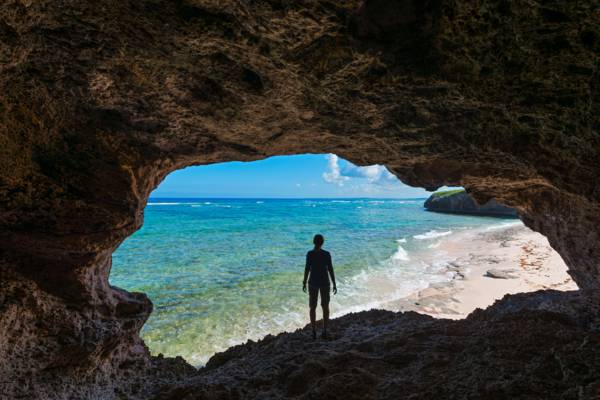 person standing in a flank margin coastal cave on an uninhabited island in the Turks and Caicos